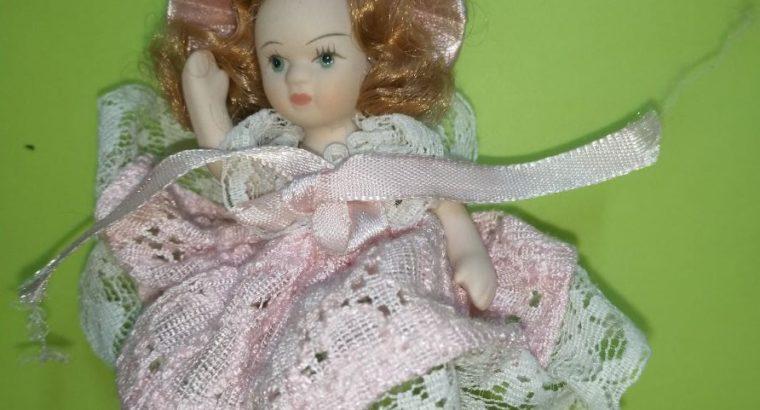 Small porcelain doll (6 cm) sitting on heart swing